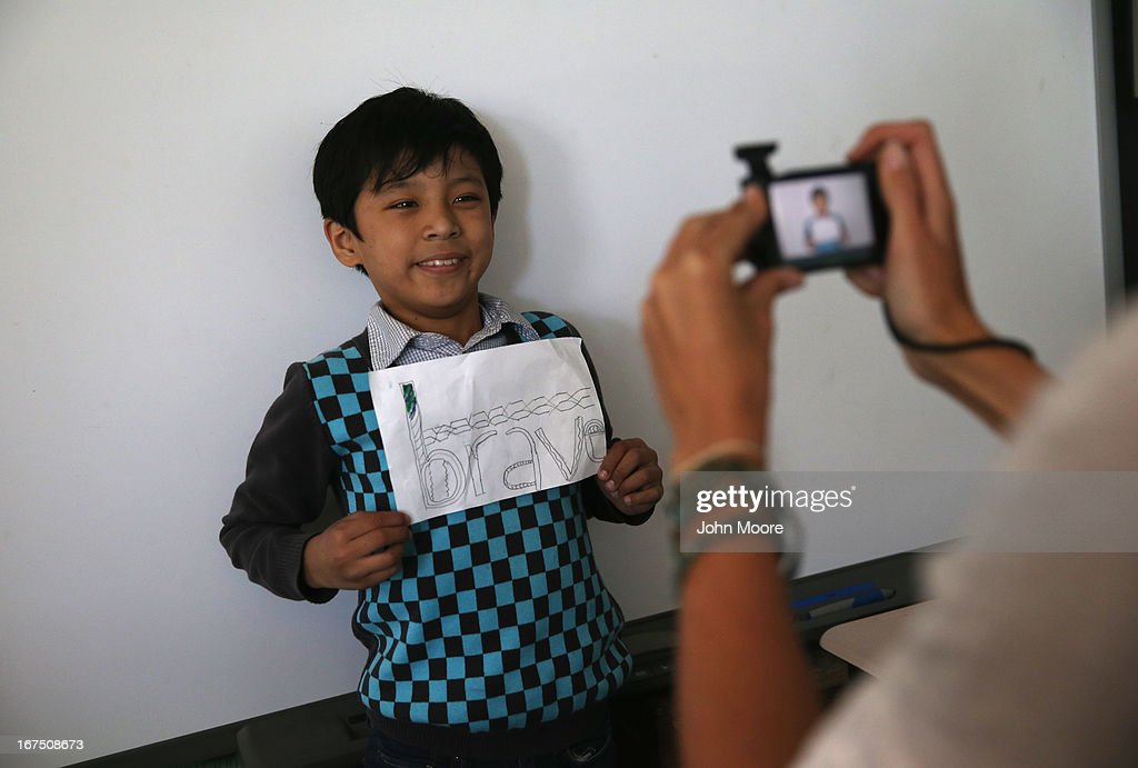 A Tibetan immigrant child displays his artwork during an after-school program for asylum immigrants run by the International Rescue Committee (IRC), on April 25, 2013 in the Queens borough of New York City. The after-school program held at P.S. 199 consists of homework help and visual art instruction for Tibetan children in grades 2 through 4. The IRC is a non-profit humanitarian aid organization that aids refugees and survivors of international conflict. They assist new arrivals, many of whom come from refugee camps and war zones, to adjust to American society after being granted refugee status and invited by the U.S. government to live in the United States. The IRC also assists refugees through the immigration and naturalization process to become U.S. citizens.