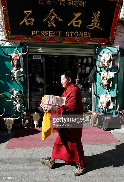 A Tibetan lama holding Buddhist scriptures walks past a store on January 5 2008 in Lhasa of Tibet Autonomous Region China With the opening of the...