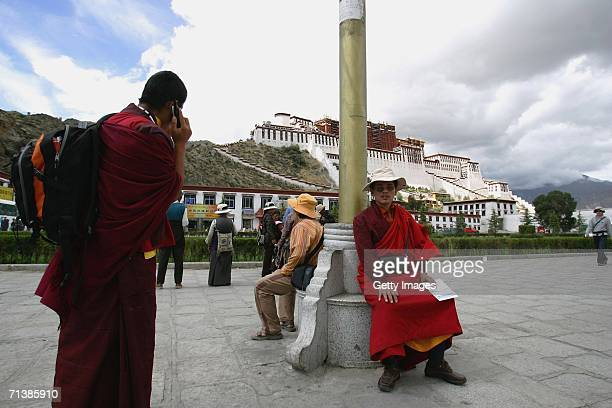 Tibetan lama uses his mobile phone in front of the Potala Palace on June 26 2006 in Lhasa Tibetan Autonomous Region China The Chinese economy is...