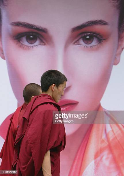 Tibetan lamas walks past a poster on June 28 2006 in Lhasa Tibetan Autonomous Region China The Chinese economy is booming and has seen rapid...