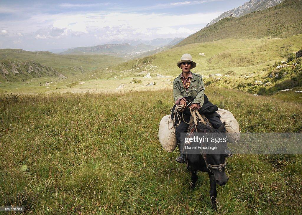 CONTENT] Tibetan man on a horse riding over the Gansu grasslands. In Langmusi, Gansu, China. September 1, 2011.