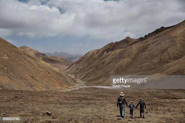 Tibetan man walks with his sons at high altitude after picking cordycep fungus on May 23 2016 on the Tibetan Plateau near Zadoi in the Yushu Tibetan...