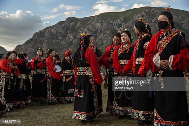 Tibetan men in traditional costume prepare for a fire dance at a local festival on July 27 2015 on the Tibetan Plateau in Yushu County Qinghai China...