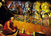 A Tibetan monk prays in front of Buddha statues inside the Sera monastery in Lhasa on June 22 2008 Chinese officials on June 22 abruptly cancelled a...