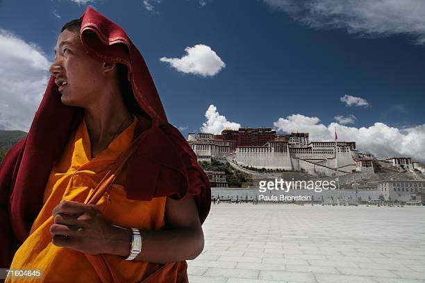 Tibetan monk stands in front of the Potala palace August 6 2006 in Lhasa in the Tibet Autonomous Region China Lhasa's face is ever changing as it...