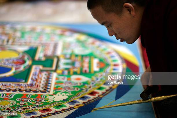 Tibetan monk works on creating an intricate sand drawing known as a mandala at the Broward County Main Library February 6 2007 in Fort Lauderdale...
