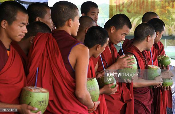 Tibetan monks drink coconuts as they break their 24hour hunger strike near the Indira Maidan on the outskirts of Siliguri on April 17 2008 Some 60...