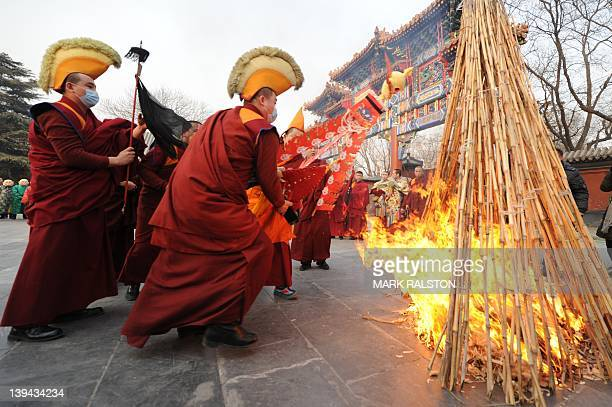 Tibetan monks throw a skull effigy into flames during a Tibetan New Year ceremony at the Yonghe Temple also known as the Lama Temple in Beijing on...