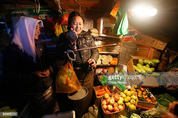 A Tibetan nomad buys vegetables in a market along the QinghaiTibet railway on December 7 2008 in Damxung County of Tibet Autonomous Region China The...