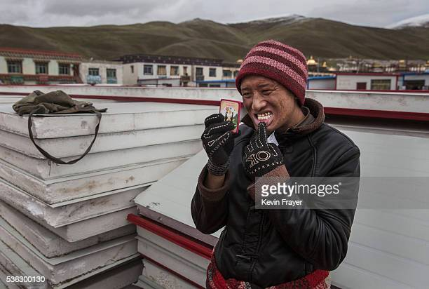 Tibetan nomad checks a fake gold cap that he had put on a tooth by a street dentist during a break from harvesting cordycep fungus on the 15th day of...