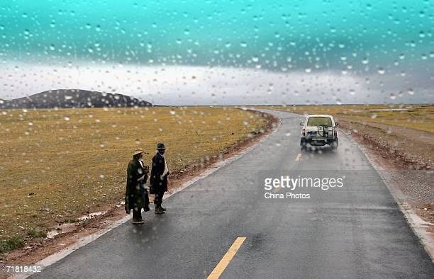 Tibetan nomads wait for cars at a road on August 27 2006 in Lhasa of Tibet Autonomous Region China Chinese tourists are flooding into Tibet this...