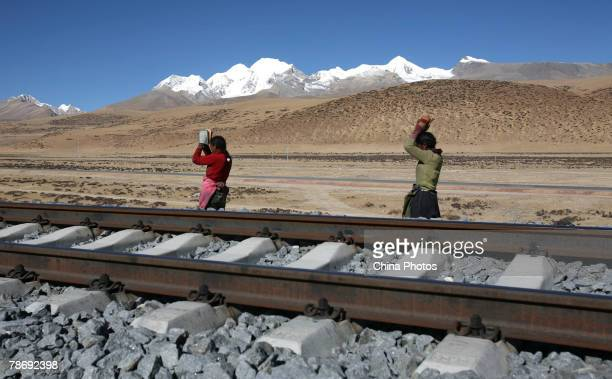 Tibetan people pray near the QinghaiTibet Railway on January 1 2008 in Dangxiong County of Tibet Autonomous Region China With the opening of the...