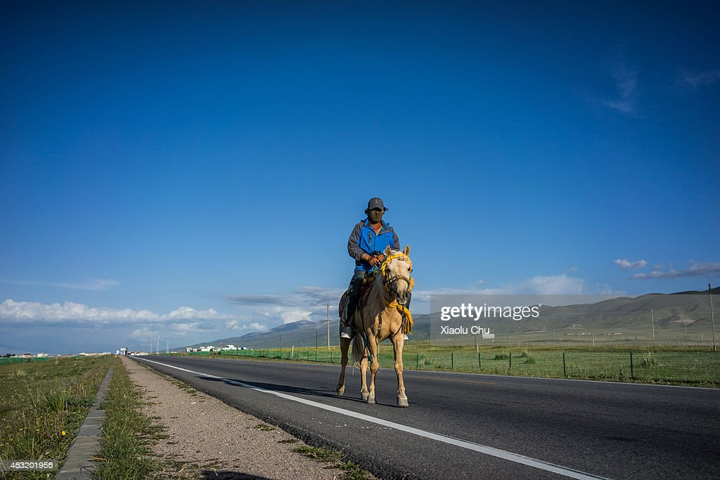 A tibetan people rides horse on road at the shore of Qinghai Lake Qinghai Lakethe sacred lake of the Tibetan Buddhism is the largest salt lake in...