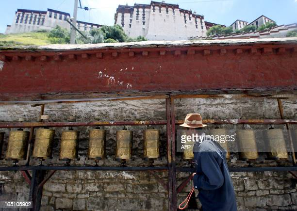 A Tibetan pilgrim spins the prayer wheels as he encircles the Potala Palace in Lhasa 26 August 2003 If Chinese authorities allow the exiled Dalai...