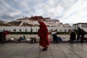 Tibetan pilgrims prostrate themselves in front of the Potala Palace as a Tibetan Buddhist monk walks past on June 21 2009 in Lhasa Tibet Autonomous...