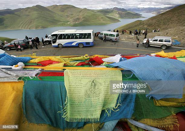 WITH 'CHINATIBETECONOMYSOCIETY ' Tibetan prayer flags flutter in the wind at Kambala Pass at 4794 meters above sea level as tour buses and other...