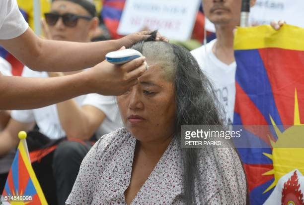 A Tibetan protester shaves the head of a Tibetan woman during a rally to mark the 57th Tibetan National Uprising Day at Martin Place in Sydney on...
