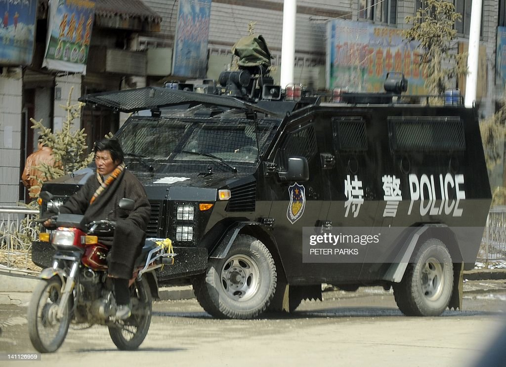 A Tibetan rides past a police armoured personnel carrier on a street in the county town of Banma in China's northwest Qinghai province on March 10, 2012. Chinese President Hu Jintao stressed the need to maintain stability in Tibet as he met legislators from the restive region, following a spate of self-immolations in Tibetan-inhabited areas. AFP PHOTO/Peter PARKS