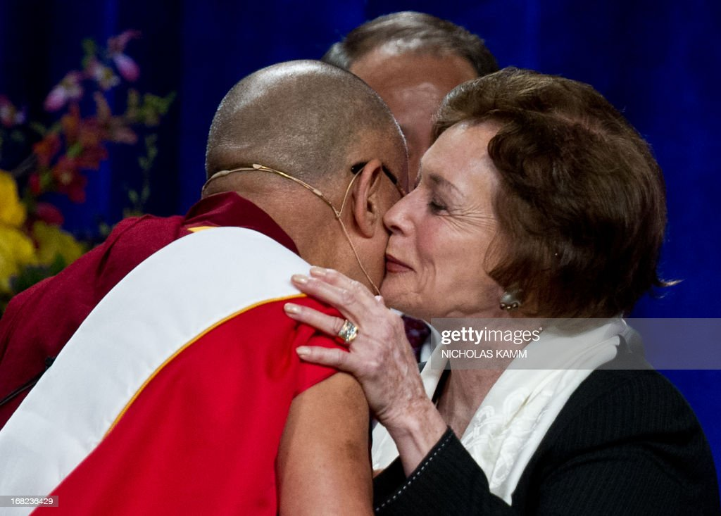 Tibetan spiritual leader the Dalai Lama greets Jihan Sadat, widow of slain Egyptian president Anwar Sadat, after delivering the Sadat Lecture for Peace, entitled 'Peace Through Compassion: Connecting a Multi-Faith World,' at the University of Maryland in College Park, Maryland, on May 7, 2013. AFP PHOTO/Nicholas KAMM