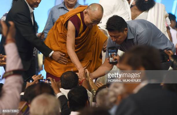 Tibetan spiritual leader The Dalai Lama greets people during a inter faith religious conclave ahead of India's 70th anniversary of Independence in...