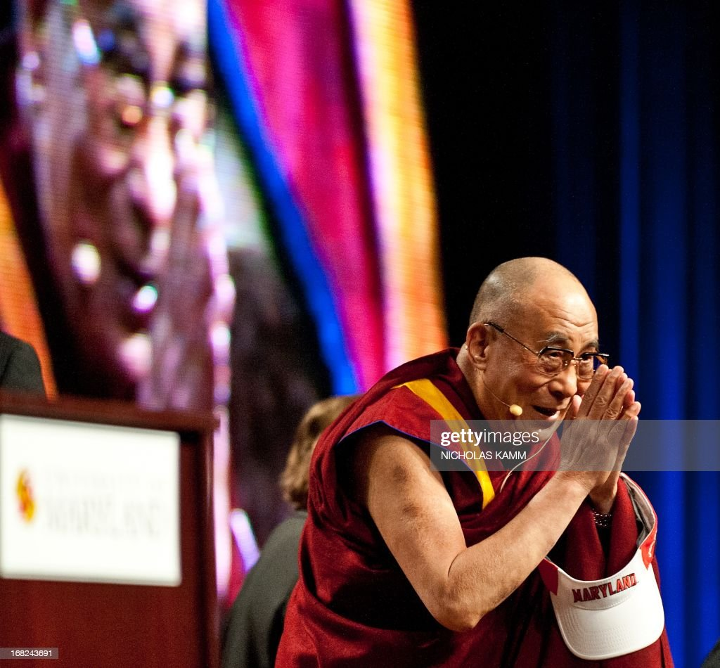Tibetan spiritual leader the Dalai Lama greets the audience before delivering the Sadat Lecture for Peace, entitled 'Peace Through Compassion: Connecting a Multi-Faith World,' at the University of Maryland in College Park, Maryland, on May 7, 2013. AFP PHOTO/Nicholas KAMM