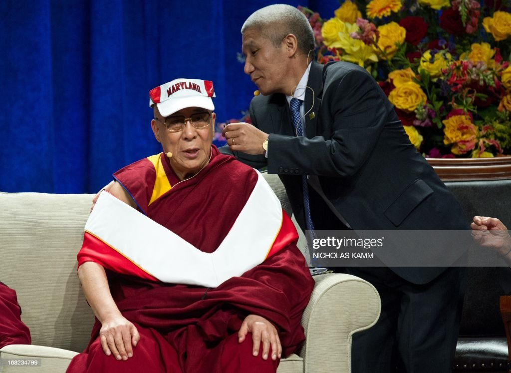 Tibetan spiritual leader the Dalai Lama is helped by an aide to adjust his sash after receiving an honorary doctorate during the Sadat Lecture for Peace, entitled 'Peace Through Compassion: Connecting a Multi-Faith World,' at the University of Maryland in College Park, Maryland, on May 7, 2013. AFP PHOTO/Nicholas KAMM