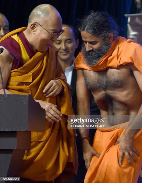 Tibetan spiritual leader The Dalai Lama looks on as Indian yoga guru Baba Ramdev demonstartes his skills of muscle control during a inter faith...