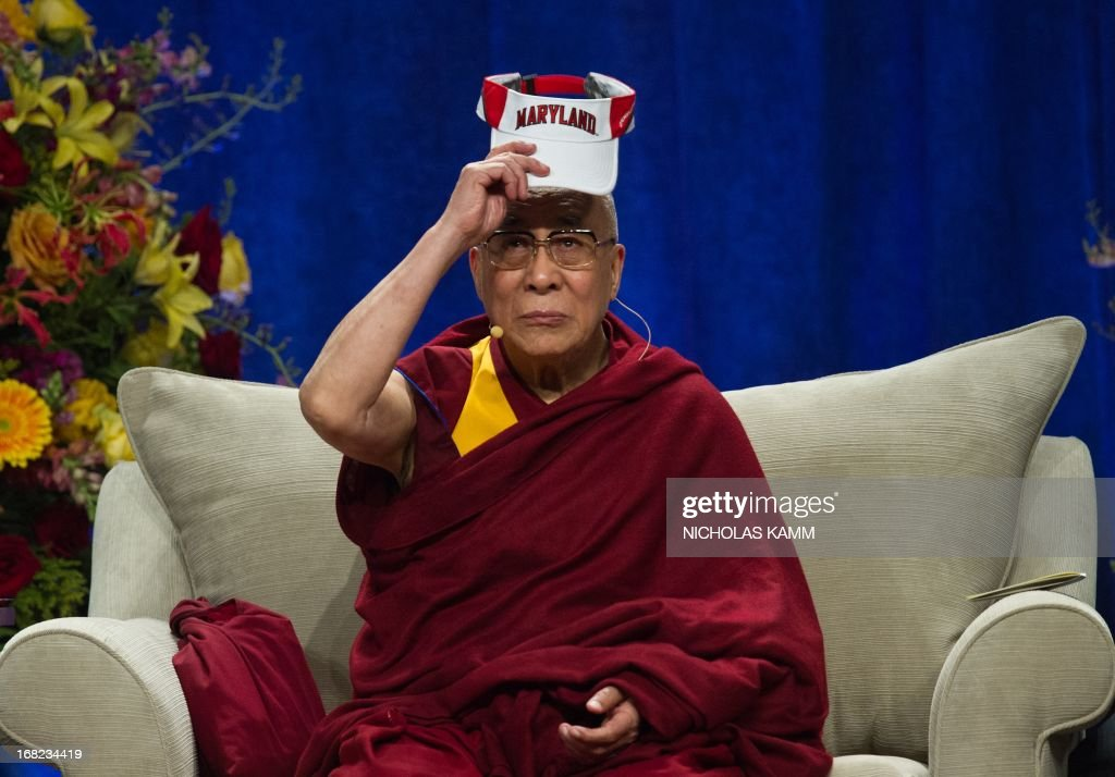 Tibetan spiritual leader the Dalai Lama puts on a Maryland visor before delivering the Sadat Lecture for Peace, entitled 'Peace Through Compassion: Connecting a Multi-Faith World,' at the University of Maryland in College Park, Maryland, on May 7, 2013. AFP PHOTO/Nicholas KAMM