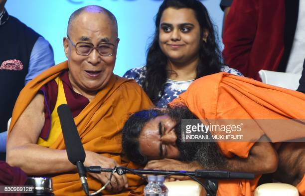 Tibetan spiritual leader The Dalai Lama reacts as Indian Yoga Guru Baba Ramdev shares a light moment during a inter faith religious conclave ahead of...