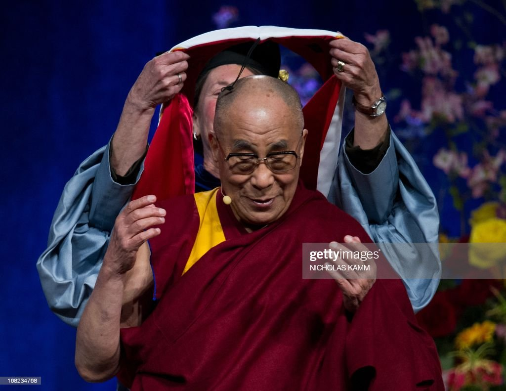 Tibetan spiritual leader the Dalai Lama receives an honrary doctorate after delivering the Sadat Lecture for Peace, entitled 'Peace Through Compassion: Connecting a Multi-Faith World,' at the University of Maryland in College Park, Maryland, on May 7, 2013. AFP PHOTO/Nicholas KAMM