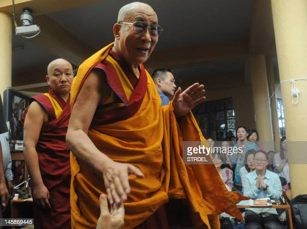 Tibetan spiritual leader The Dalai Lama shakes hands of devotees as the leaves the Tsuglakhang Temple in McLeod Ganj in Dharamsala on June 7 2012...