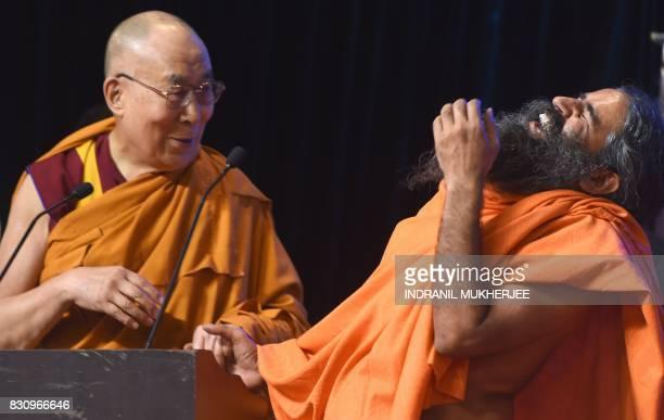 Tibetan spiritual leader The Dalai Lama smiles as Indian yoga guru Baba Ramdev laughs during a inter faith religious conclave ahesd of India's 70th...