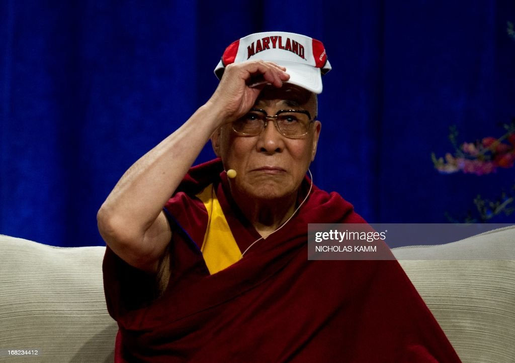 Tibetan spiritual leader the Dalai Lama wears a Maryland visor before delivering the Sadat Lecture for Peace, entitled 'Peace Through Compassion: Connecting a Multi-Faith World,' at the University of Maryland in College Park, Maryland, on May 7, 2013. AFP PHOTO/Nicholas KAMM