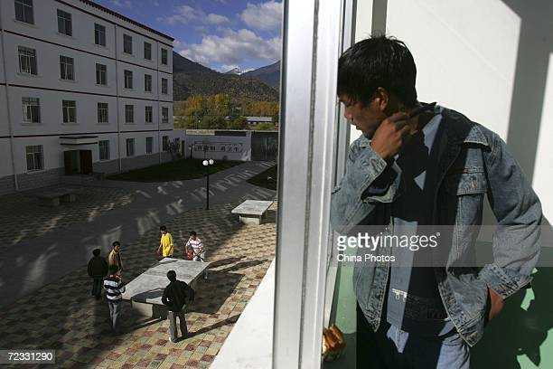 A Tibetan student in a dormitory looks at his classmates playing table tennis at Nyingchi First High School the only high school of Nyingchi...
