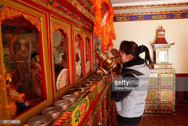 A Tibetan villager dedicates water to Buddha in her new home in Liuwu Village where the Lhasa Railway Station a terminal of the QinghaiTibet railway...