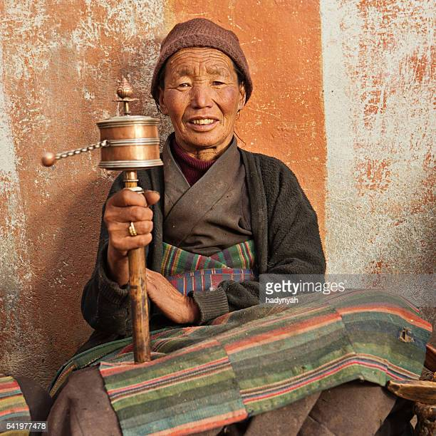 Tibetan woman holding praying wheel in Upper Mustang, Nepal