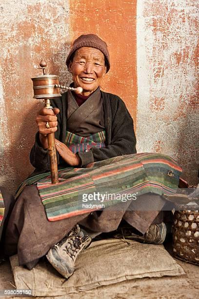Tibetan woman holding praying wheel, Upper Mustang