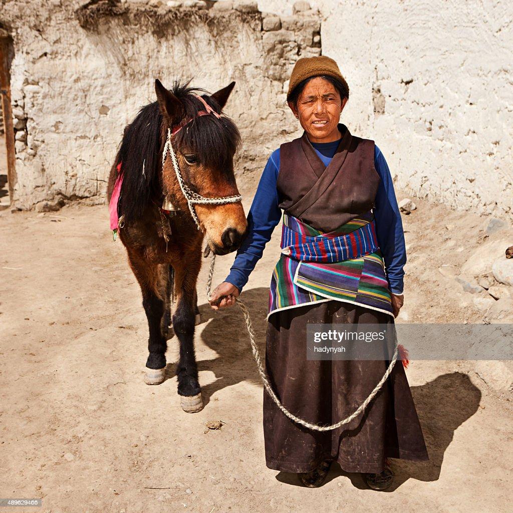Tibetan woman leads her horse in Upper Mustang