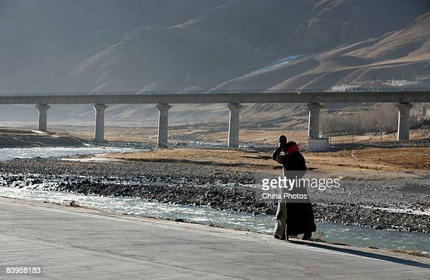 A Tibetan woman prays to make pilgrimage to Lhasa on a road along the QinghaiTibet railway on December 7 2008 in Damxung County of Tibet Autonomous...