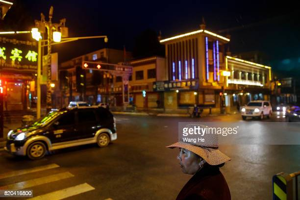 A Tibetan woman prepares to cross the road on July 21 2017 in Litang County Ganzi Tibetan Autonomous Prefecture Sichuan Province China Litang County...