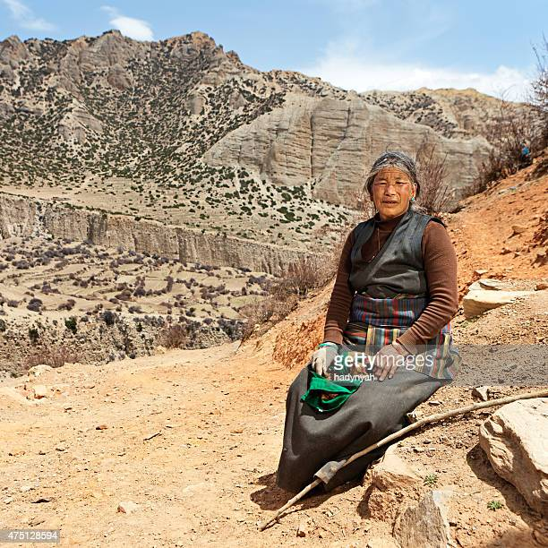 Tibetan woman sitting on the rock. Mustang, Nepal.