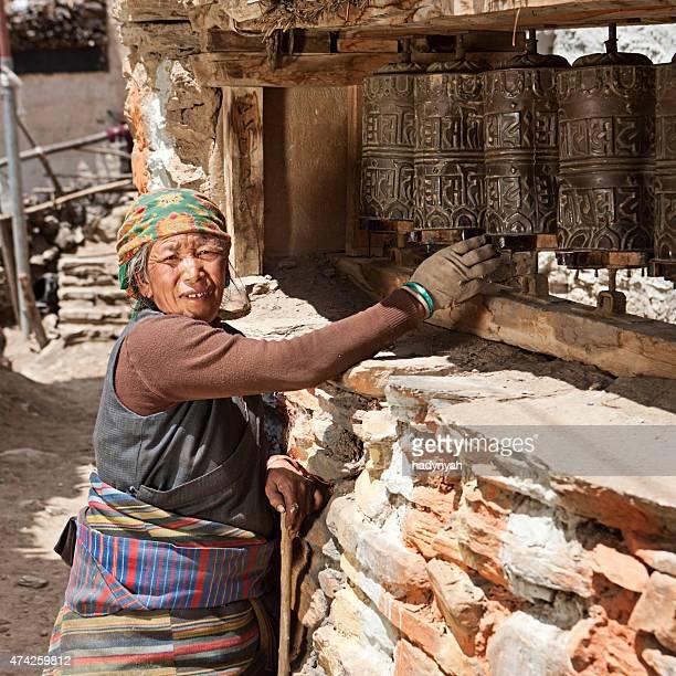 Tibetan woman spinning a prayer wheel. Mustang, Nepal