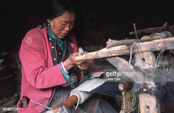 Tibetan woman using a hand loom to weave a scarf out of yaks wool in a village on the road to Lhasa Yaks are invaluable to the Tibetans who use their...