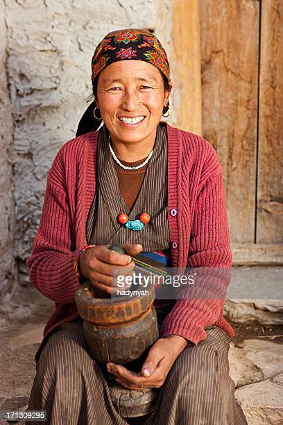 Tibetan woman using a mortar to make  flour. Mustang, Nepal