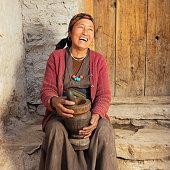 Tibetan woman using mortar