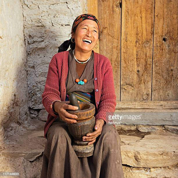 Tibetan woman using mortar