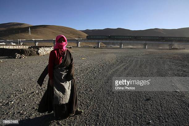 A Tibetan woman walks near the QinghaiTibet Railway on January 1 2008 in Dangxiong County of Tibet Autonomous Region China With the opening of the...
