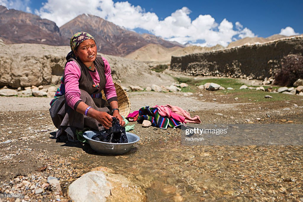 Tibetan woman washing clothes in the river. Mustang. : Stock Photo