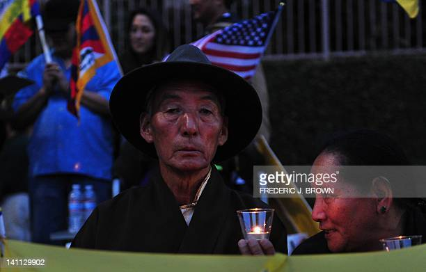 Tibetans and supporters of a 'Free Tibet' hold placards during a candlelight vigil in front of the Chinese Consulate Los Angeles on March 10 2012 in...