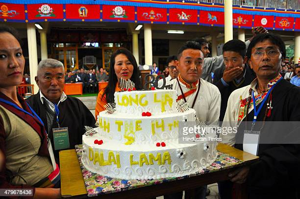 Tibetans hold the birthday cake going to distribute the cake during the celebrations to mark 80th birth anniversary of Dalai Lama at Tsuglagkhang...